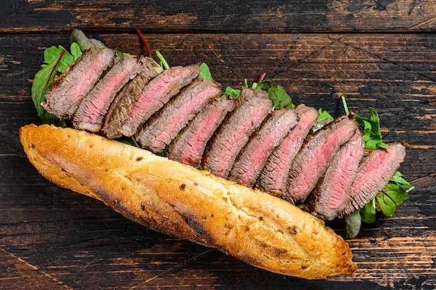 Grilled baguette steak sandwich with arugula and cheese