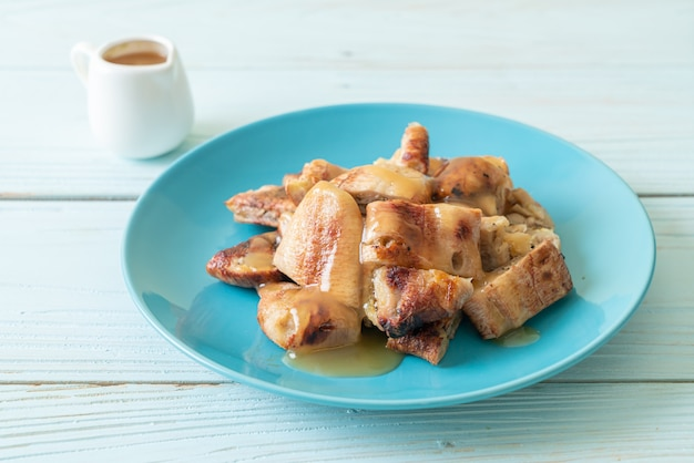 Grilled bananas with coconut caramel sauce on plate
