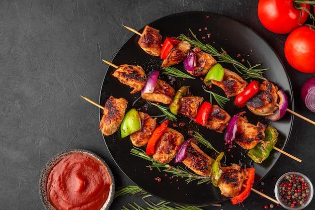 黒い表面のプレートに野菜、スパイス、バジル、トマトのケチャップを添えた串焼きのバーベキュー肉のグリル