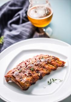 술집이나 레스토랑의 메뉴로 하얀 접시에 구운 바베큐 돼지 갈비.