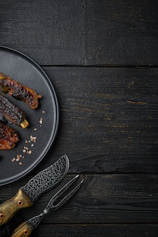 Grilled barbecue pork ribs set, on plate, with barbeque knife and meat fork, on black wooden table