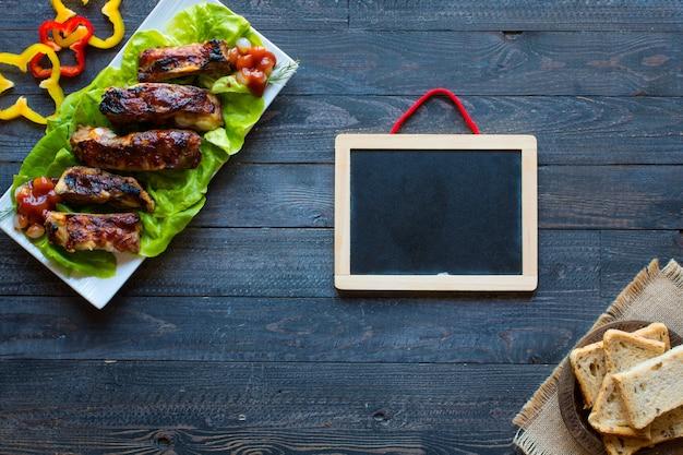 Барбекю на гриле свиные ребрышки с овощами на деревянном столе