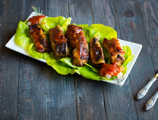 Grilled barbecue pork ribs with vegetables on a wooden table
