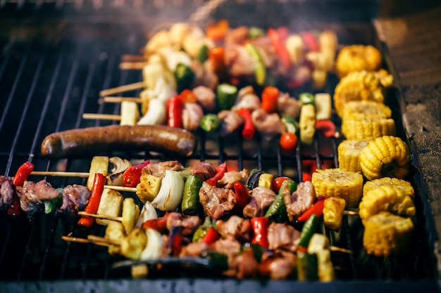 Grilled barbecue skewers kebabs with vegetables on the flaming grill