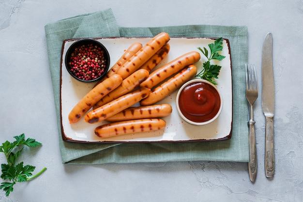 어두운 콘크리트 테이블에 세라믹 접시에 소스와 케첩, 마늘과 구운 바베큐 소시지.