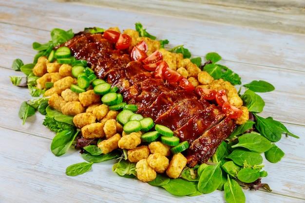 Запеченные ребрышки на гриле с зеленым салатом и картофелем.