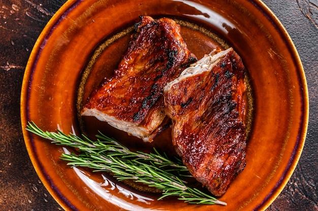 접시에 구운 바베큐 송아지 고기 짧은 갈비 고기. 어두운 배경입니다. 평면도.