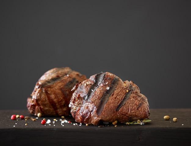 Стейк из филе говядины на черной деревянной разделочной доске