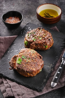 Grilled beef fillet steaks with herbs and spices on stone slate. two fillet mignon. fillet of beef.