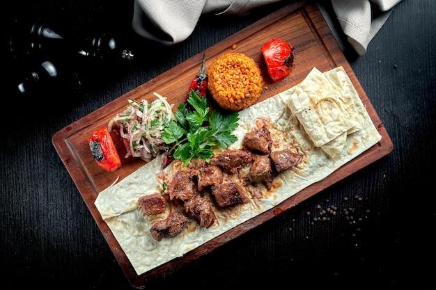 Bulgur와 야채 나무 보드에 garnished 구운 된 쇠고기 등심. 터키 케밥. 클로즈업, 선택적 초점