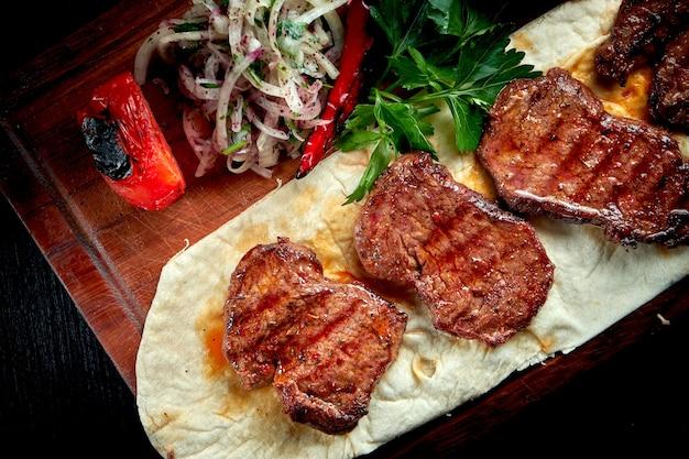 Bulgur와 야채 나무 보드에 garnished 구운 된 쇠고기 등심. 터키 케밥.