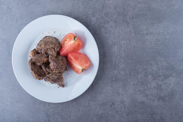 하얀 접시에 구운 쇠고기 케밥과 토마토.
