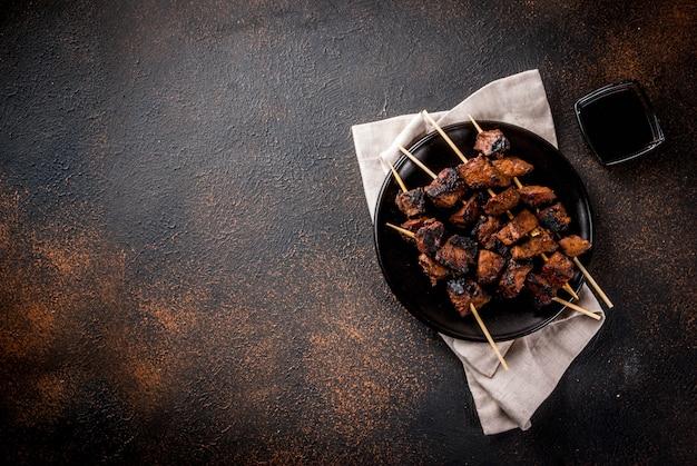 어두운 테이블에 꼬치에 구운 쇠고기 간