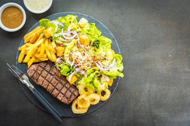 Grilled beef meat steak with french fries onion ring