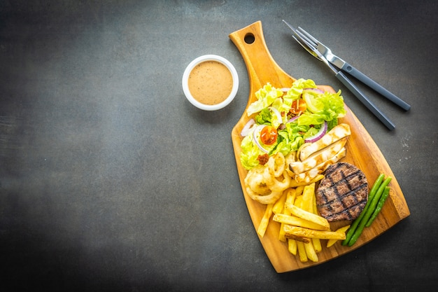Grilled beef meat steak with french fries sauce and fresh vegetable