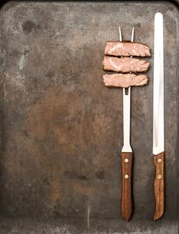 금속 주방 책상에 포크와 나이프로 구운 쇠고기 고기. 음식 배경