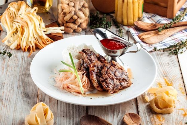 牛肉のグリル、ライスと木製の装飾が施されたテーブルに赤いソース