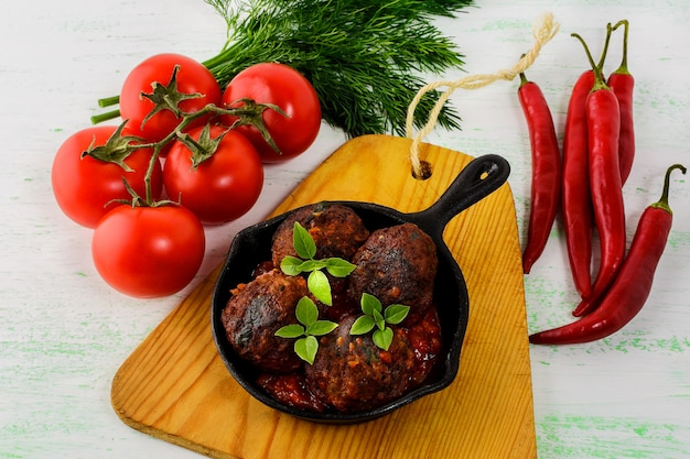 Grilled beef meatballs with chili pepper  served in skillet