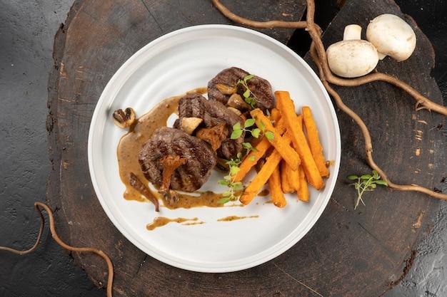 Медальоны из говядины на гриле с гарниром из сладкого картофеля и грибным соусом из грибов. основное горячее мясное блюдо. стейк из телятины или свинины