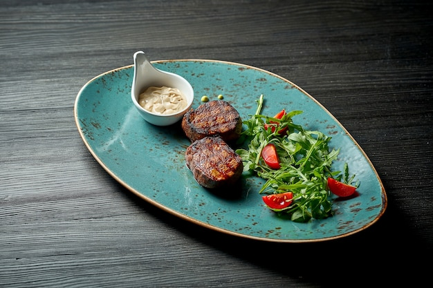 Медальоны из говядины на гриле с салатом и белым соусом.