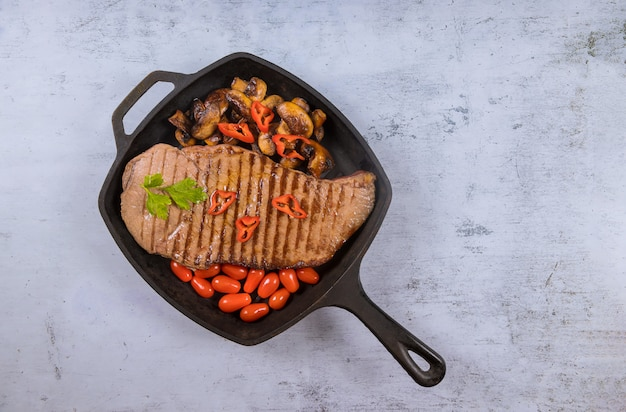 Grilled beef sirloin steaks with vegetable in grill pan.