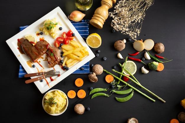 Жареный стейк из говядины и картофельные овощи на фоне темного деревянного стола, вид сверху. сочное мясное блюдо с соусом, картофелем, перцем и столовыми приборами на диске. еда в ресторане