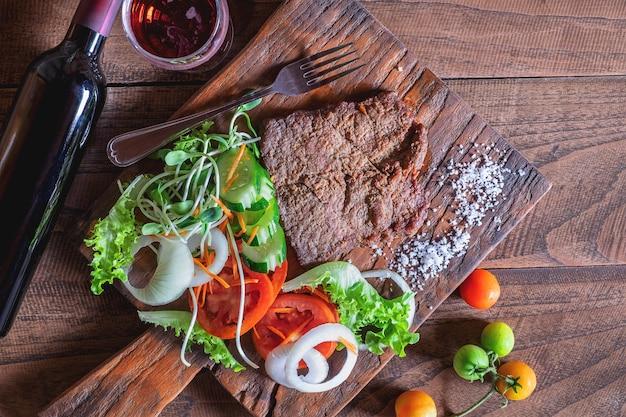 Жареный бифштекс и соль на деревянной разделочной доске