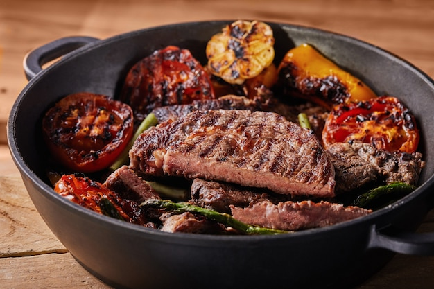 Grilled beef steak in a black pan with baked vegetables - tomatoes, asparagus, garlic and peppers