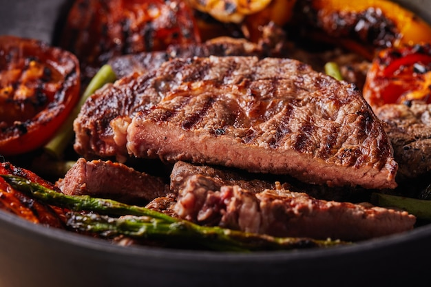 Grilled beef steak in a black pan with baked vegetables