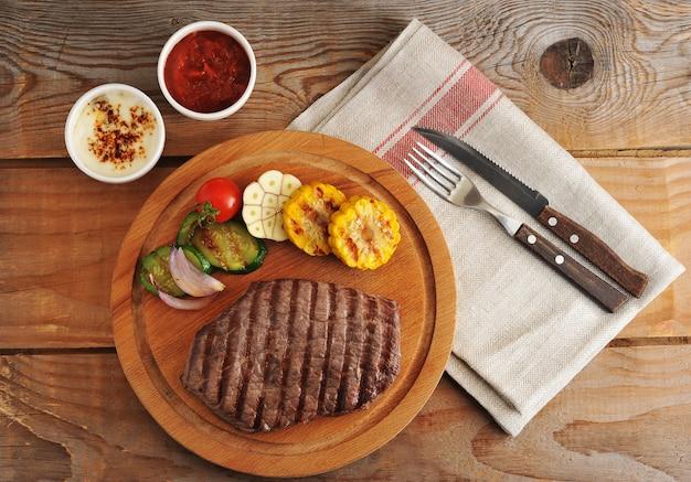 Стейк из говядины гриль, нарезанный на кусочки, овощи гриль - цуккини, кукуруза, лук, чеснок, вишня