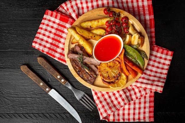 Bistecca di manzo alla griglia sulla superficie di legno scuro.