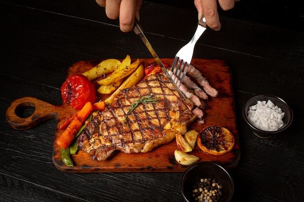 Grilled beef steak on the dark wooden surface.