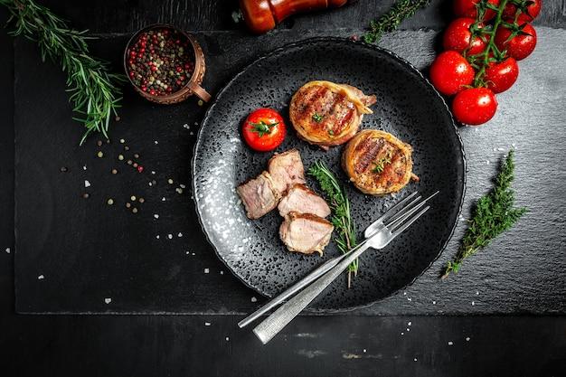 구운 쇠고기 스테이크. 필레 미뇽 쇠고기 안심 스테이크에 향신료를 뿌린 베이컨. 긴 배너 형식입니다. 평면도.