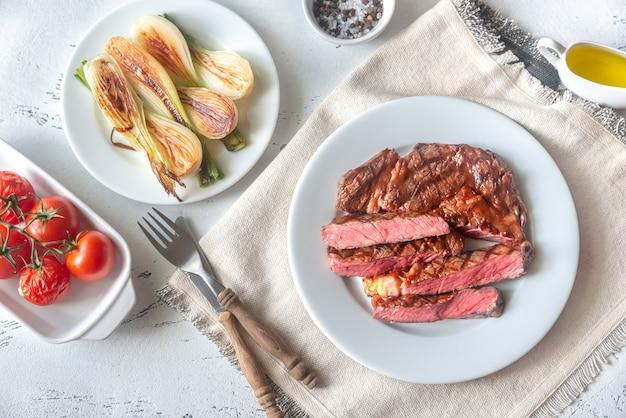 Стейк из говядины на гриле, украшенный свежим салатом, луком и помидорами черри