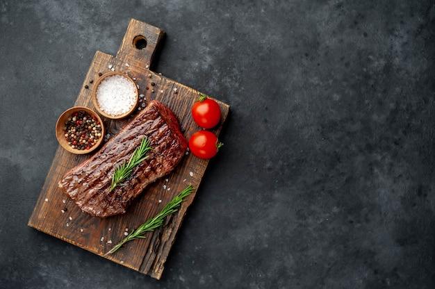 Стейк из говядины на деревянной доске со специями на каменном фоне с копией пространства для вашего текста