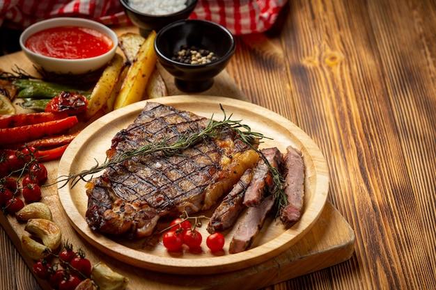 Стейк из говядины на темной деревянной поверхности.