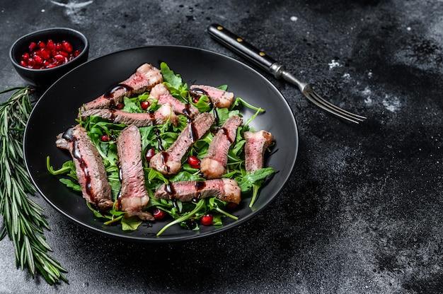 ルッコラ、ザクロ、緑の野菜を添えたビーフステーキのグリルサラダ。黒の背景。上面図。スペースをコピーします。