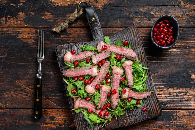 ルッコラ、ザクロ、緑の野菜のグリルビーフステーキサラダ