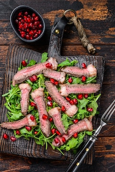 Grilled beef steak salad with arugula, pomegranate and greens vegetables.
