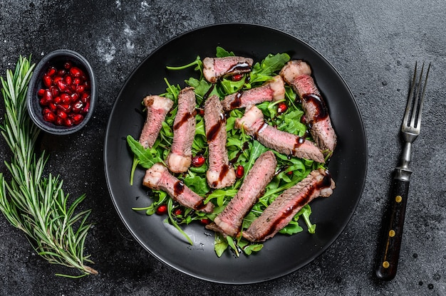Grilled beef steak salad with arugula, pomegranate and greens vegetables