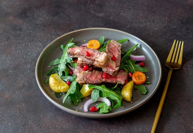 ルッコラ、ジャガイモ、ニンジン、玉ねぎ、ザクロのグリルビーフステーキサラダ。健康的な食事。ダイエット。