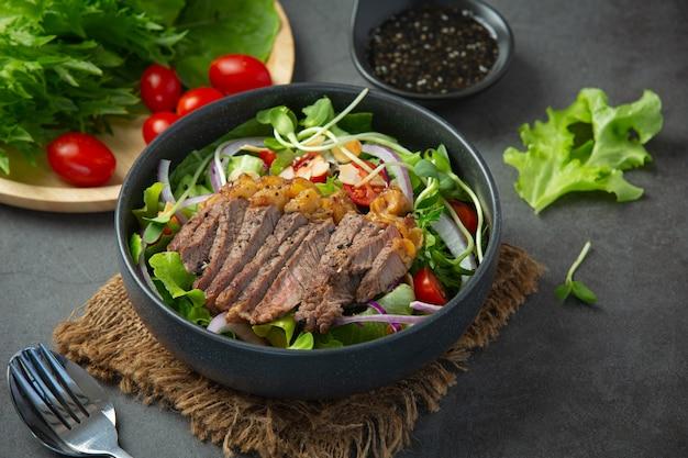 Салат из говяжьего стейка на гриле с овощами и соусом. здоровая пища.