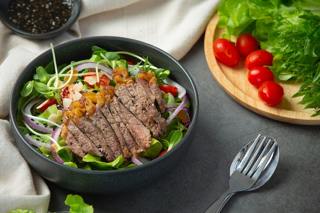 Grilled beef steak salad with vegetables and sauce. healthy food.