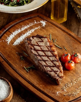 Grilled beef steak served with salt herbs and grilled tomato