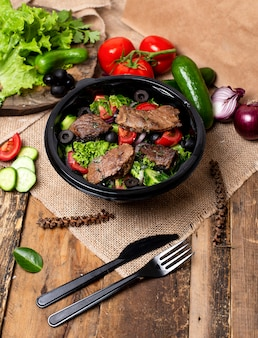 Grilled beef steak slices with green salad, tomatoes and olives