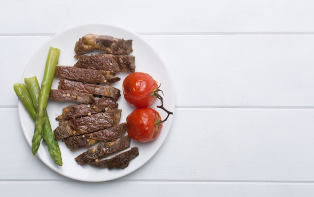 Grilled beef steak on a white plate and white background, flat lay and copy space