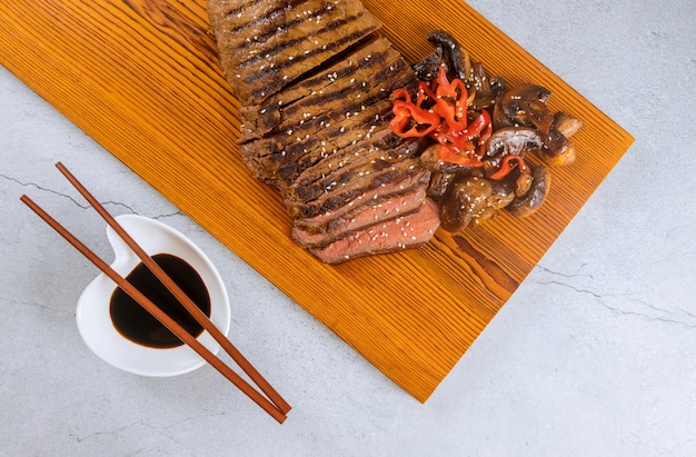 Grilled beef steak with chopstick on cutting board.