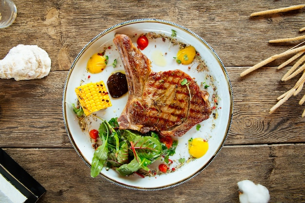 Grilled beef steak with corn on wooden background