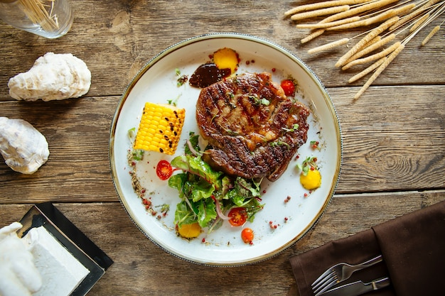 Grilled beef steak with corn on wooden surface