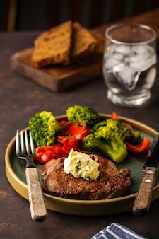 Стейк из говядины на гриле с чесночным маслом и овощами. мясо с жареным болгарским перцем, брокколи и луком.